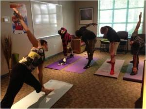 """Manuel Vicens - Elizabeth Auten, left, founder of the Shakti Youth Project, leads a yoga session in a multipurpose classroom at the Argus House, a group home for at-risk teenage boys in Arlington County. """"I started sharing yoga with them and found that was a great catalyst for other conversations,"""" Auten said. """"As we worked on poses together, we could talk about life lessons and how to try something new that you've never tried before — how to be uncomfortable."""""""